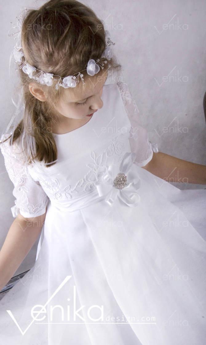 Lace Communion dress behind a decorative flower in the waist